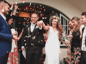 bride and groom celebrate with a flower petal exit after their wedding